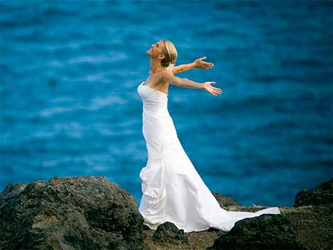 Bride on lava rocks next to the ocean