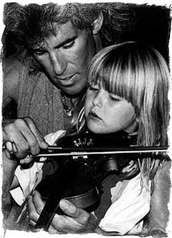 Don V Lax, classical violinist, teaching a young girl