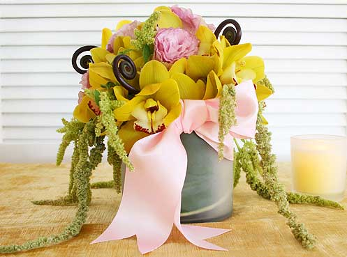 This lovely arrangement combines yellow cymbidium orchids, pink lisianthus, uluhe fern and cascading